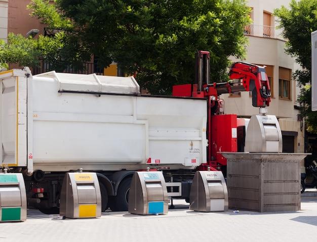 Przetwarzający ciężarówkę podnosi kosz przy miastem