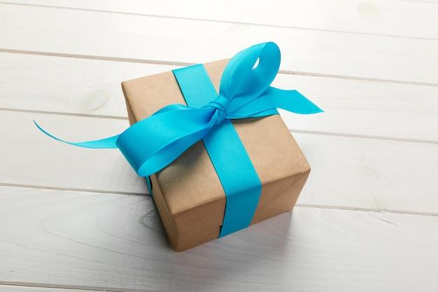 Przetwarzający papierowy prezenta pudełko z błękitnym faborkiem na starym drewnianym białym tle odgórny widok