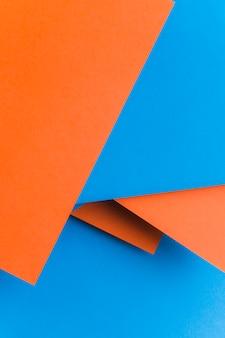 Przetwarzający papierowy tekstury tło w błękicie i pomarańczowym kolorze