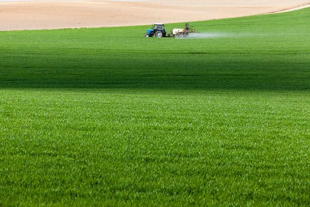 Przetwarzanie ciągnika zbożowego sfotografowanego na polu rolnym podczas przetwarzania pestycydów