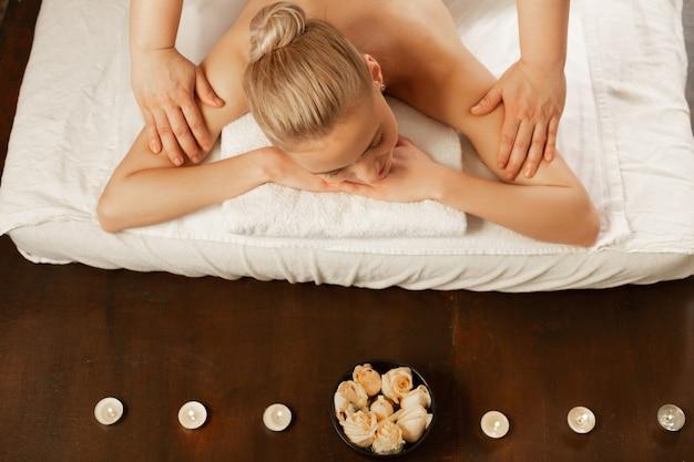 Przetwarzanie mistrza masażu. spokojna młoda dama leżąca na zadaszonym masażu przy świecach i kwiatach w pobliżu i ciesząca się ruchami