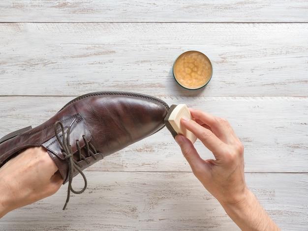 Przetwarzanie wosku do obuwia. mężczyzna czyści buty.