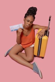 Przewidywanie. ciemnoskóra kobieta trzymająca walizkę i bilet lotniczy i wyglądająca na wyczekiwaną