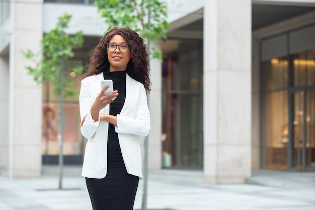 Przewijający się telefon zachwycony afrykańską bizneswoman w stroju biurowym uśmiechnięty