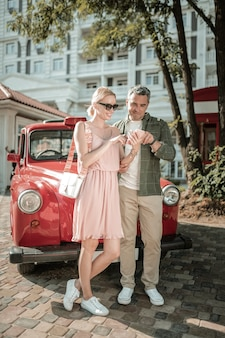 Przewijanie razem. wesoła para małżeńska stojąca na zewnątrz w pobliżu ich samochodu i używająca smartfona