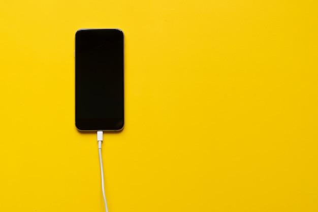 Przewód ładujący włożony do smartfona na białym tle