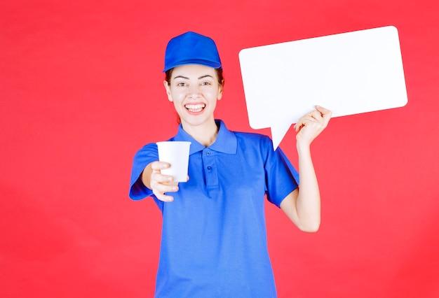 Przewodniczka w niebieskim mundurze trzymająca białą prostokątną tablicę informacyjną i oferująca uczestnikowi jednorazowy kubek napoju.