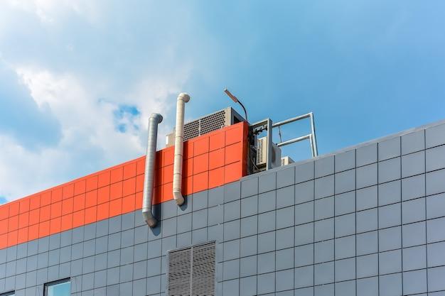 Przewody wentylacyjne i klimatyzatory znajdują się na dachu budynku produkcyjnego