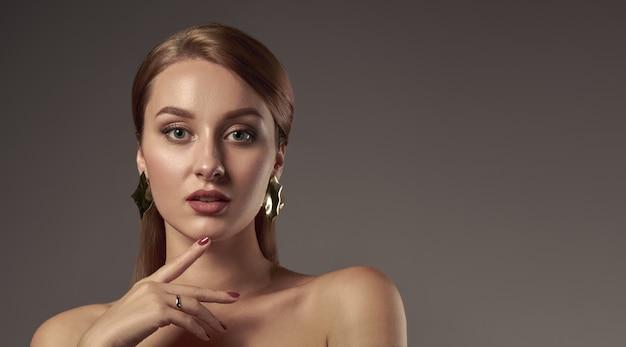 Przewodzi strzał atrakcyjna młoda dziewczyna z naturalnym makeup macania twarzą na szarym tle z kopii przestrzenią