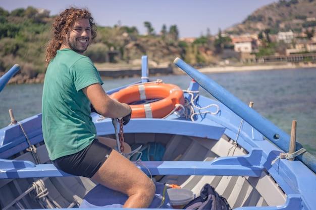 Przewoźnik wiosłuje w swojej drewnianej łodzi podczas słonecznego popołudnia