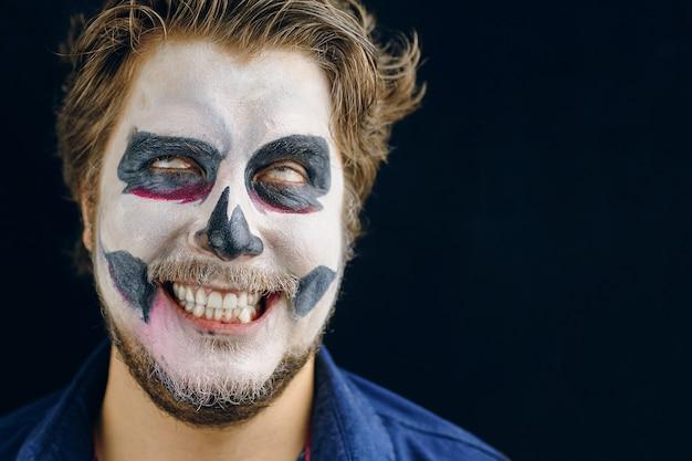 Przewrócił oczami, uśmiechnął się chytrze, rozczochrane włosy, szalone spojrzenie. makijaż człowieka w dniu śmierci na halloween. miejsce do kopiowania