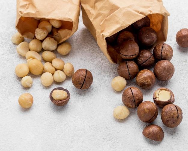 Przewrócone papierowe torby wypełnione orzechami makadamia i czekoladą