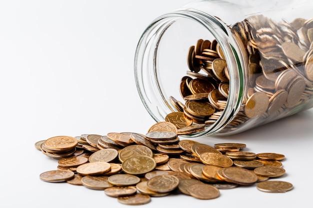 Przewrócone szkło i złote monety na białej powierzchni