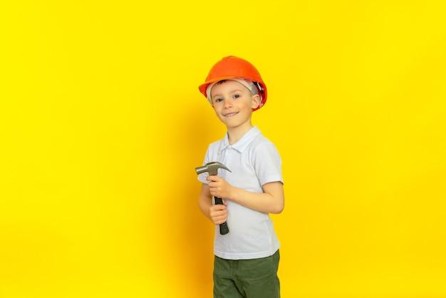 Przez całe życie budowniczy dziecka (inżynier) trzyma mleko dwiema rękami, uśmiecha się. ubrany w pomarańczowy kask budowlany