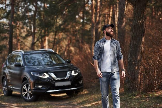 Przez drzewa wpada piękne światło słoneczne. brodaty mężczyzna w pobliżu swojego nowego czarnego samochodu w lesie. koncepcja wakacji