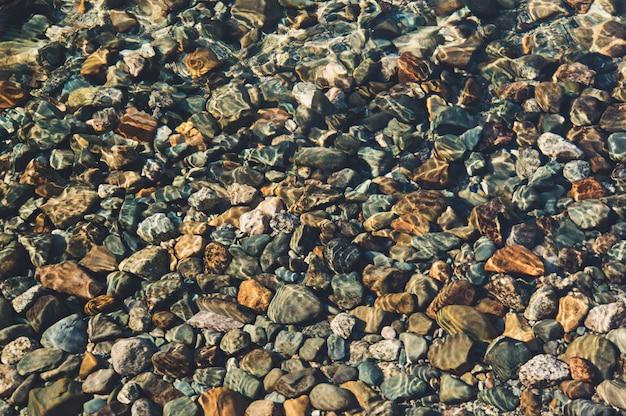 Przez grubość przezroczystej wody widać dno składające się z kamyków, kamieni, piasku. tło okrągłych kamiennych kamyków na dnie jeziora pod wodą