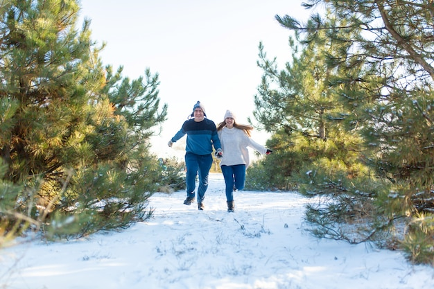 Przez las zimowy biegnie kochająca para trzymając się za ręce. śmiej się i baw się dobrze