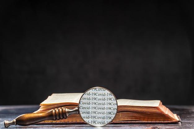 Przez lupę leżącą na stoliku obok książki odczytuje się słowa ð¡owida 19. koncepcja wiedzy o koronawirusie.
