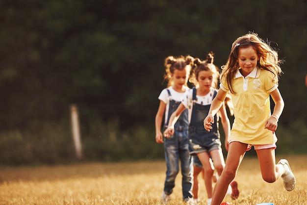 Przez przeszkody. dzieci biegają w polu w słoneczny dzień. koncepcja zdrowego stylu życia.