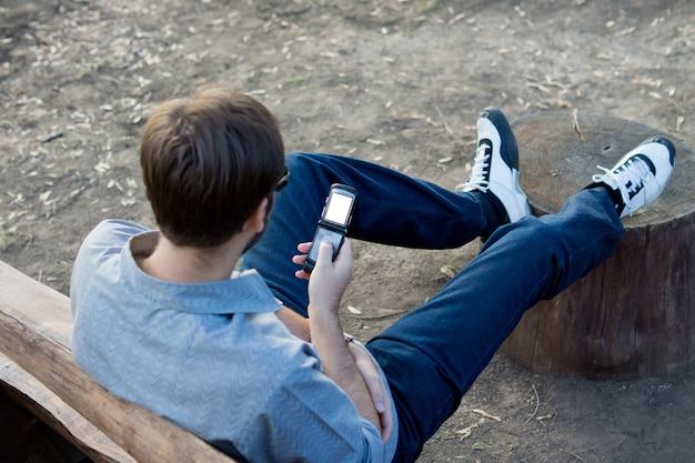 Przez ramię widok mężczyzny czytającego wiadomość tekstową na swoim telefonie komórkowym z podświetlonym ekranem
