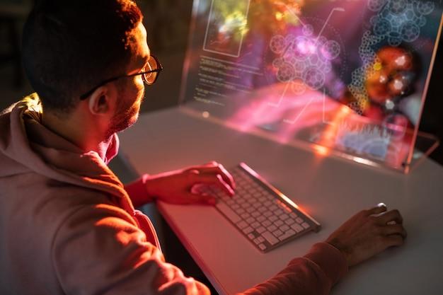Przez ramię widok młodego inżyniera w okularach siedzącego przy stole i projektującego model 3d na komputerze