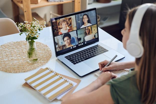 Przez ramię widok studentka dziewczyna w słuchawkach siedzi przy stole i uczestniczy w konferencji online w grupie studentów