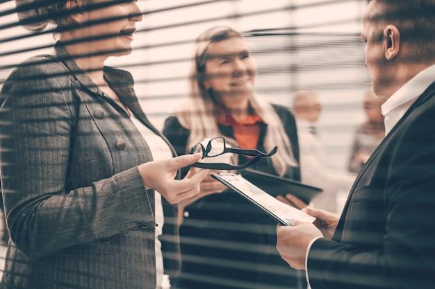 Przez rolety grupa pracowników omawiająca dokumenty biznesowe