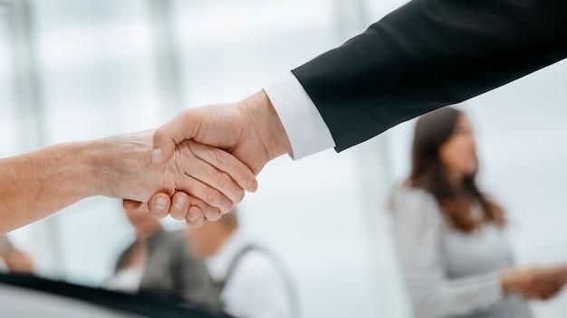 Przez rolety uścisk dłoni ludzi biznesu tło biznesowe