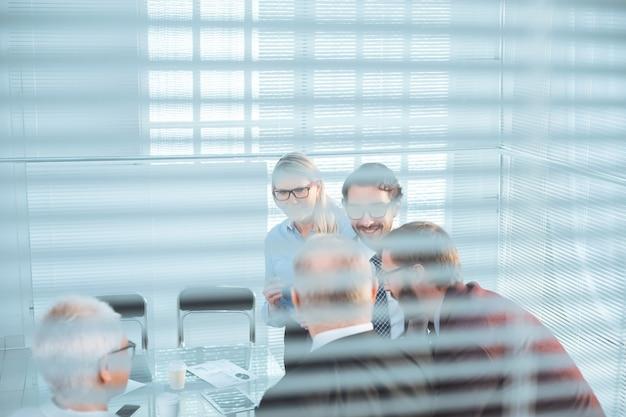 Przez rolety. zespół biznesowy omawiający kwestie biznesowe. pomysł na biznes