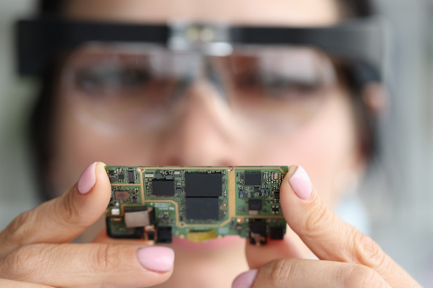 Przez soczewkę powiększającą inżynier patrzy na chip komputerowy