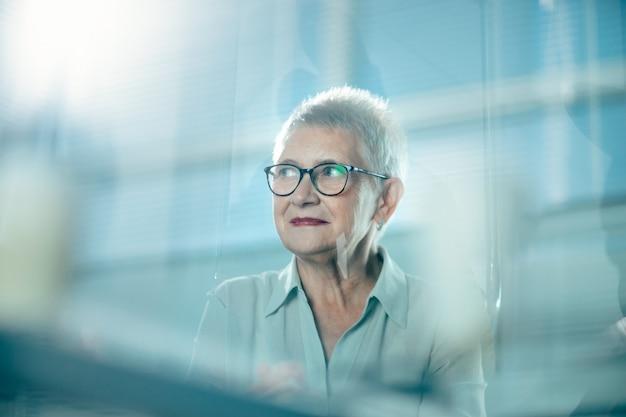 Przez szkło. doświadczona dorosła kobieta biznesu pracuje w biurze