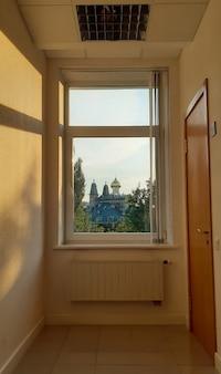 Przez zamknięte duże okno można zobaczyć kopuły drzew kościelnych i wieże budynku