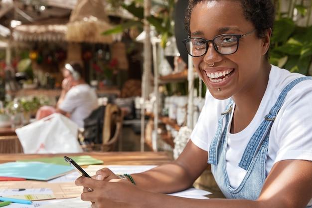 Przezabawna ciemnoskóra nastolatka używa telefonu komórkowego do aktualizacji profilu i płatności online