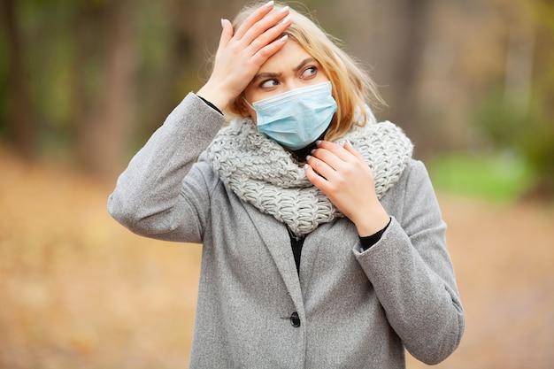 Przeziębienie i grypa. kobieta z medyczną twarzy maską przy plenerowym