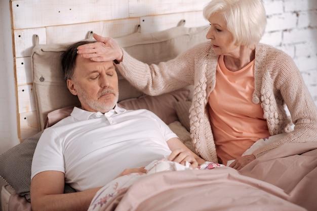 Przeziębiłeś się. starsza kobieta siedzi na łóżku obok chorego męża i czuje temperaturę jego ciała, dotykając jego czoła.