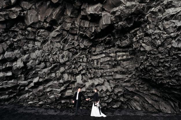 Przeznaczenie islandia ślub para ślubna pod skałą z kamieni bazaltowych narzeczeni na