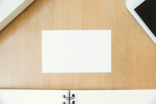 Przeznaczone do walki radioelektronicznej górę widoku fotografii pokazano puste białej wizytówki i przy użyciu nowoczesnych laptopów i telefonów komórkowych na stół drewna rozmyte tło. mockup gotowy do prywatnych informacji. poziomy makieta.