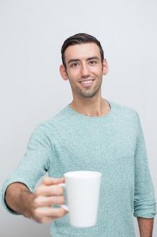 Przeznaczone do walki radioelektronicznej uśmiechnięta przystojny mężczyzna oferuje kubek herbaty