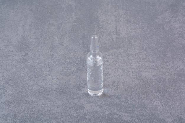 Przezroczysta ampułka medyczna na marmurowym stole.