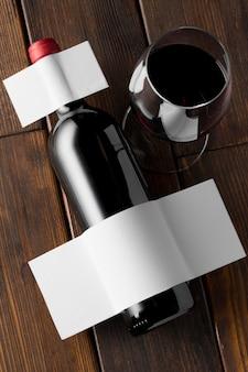 Przezroczysta butelka wina i kieliszek z pustą etykietą
