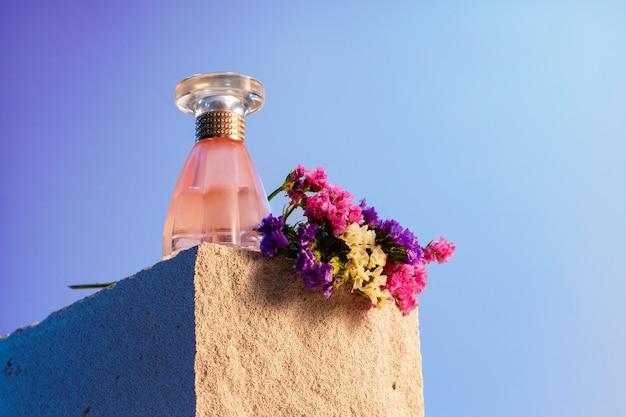 Przezroczysta butelka zapachowa na szarym bloku żużlowym