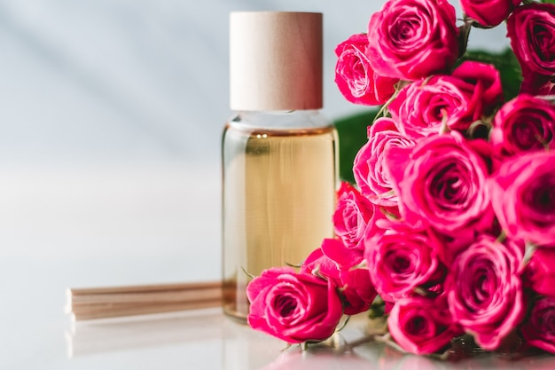 Przezroczysta butelka żółtego oleju lub perfum z drewnianymi patyczkami i delikatnymi różowymi różyczkami na białej powierzchni. koncepcja salonu spa i procedur. skopiuj miejsce