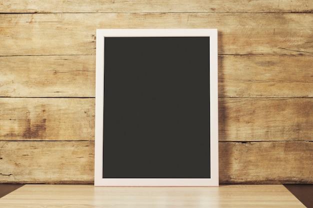 Przezroczysta ciemna tablica z ramą na drewnianej powierzchni. skopiuj miejsce