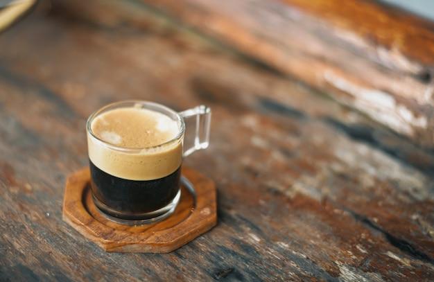 Przezroczysta filiżanka kawy umieszczona jest na brązowej lakierowanej drewnianej powierzchni z naturalnie rozmytym tłem.