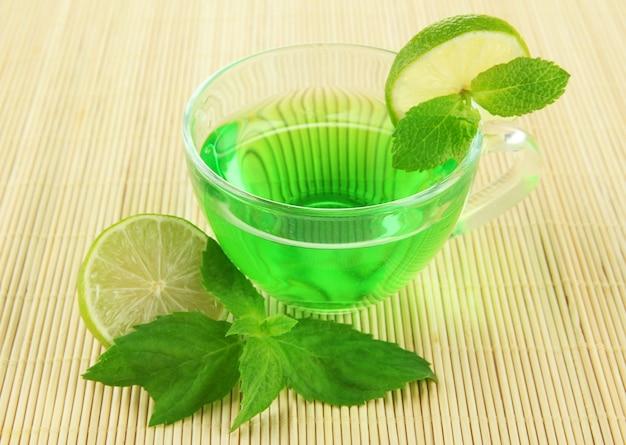 Przezroczysta filiżanka zielonej herbaty z limonką i miętą na bambusowej powierzchni