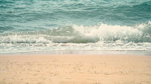 Przezroczysta jasnoniebieska woda morska lub płynne falowanie morskie i rozpryskiwanie do jasnobrązowego piasku;