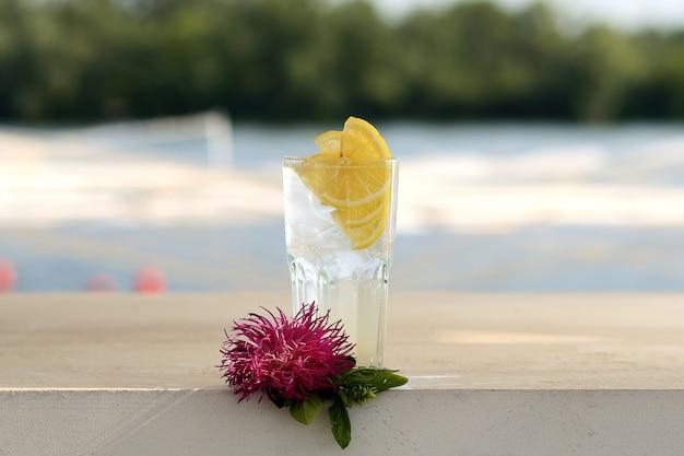 Przezroczysta lemoniada z lodem i cytryną w szklanej zlewce. z kwiatowym wystrojem