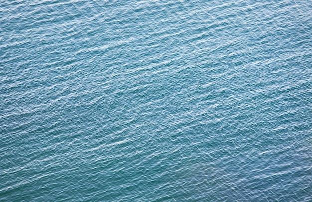 Przezroczysta przybrzeżna lazurowa powierzchnia wody z kilkoma kamieniami na dnie