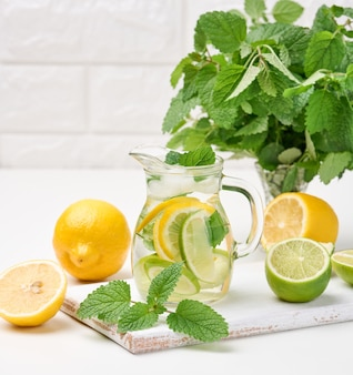 Przezroczysta szklana karafka z plasterkami cytryny, limonki i liści mięty na białym stole, detox. za składnikami napoju