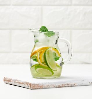 Przezroczysta szklana karafka z plasterkami cytryny, limonki i liści mięty na białym stole, detox